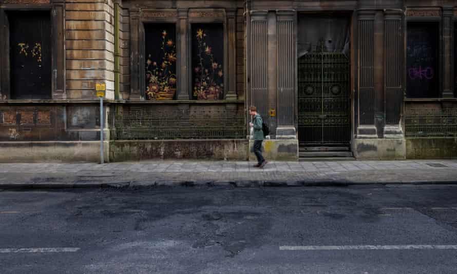 Man walks past the remnants of van