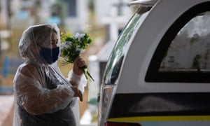 A relative of a coronavirus victim holds flowers next to a hearse at the Nossa Senhora Aparecida cemetery in Manaus, Amazonas state, Brazil, on January 13, 2021.