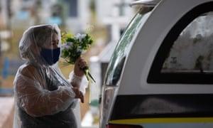 A relative of a coronavirus victim holds flowers next to a hearse at the Nossa Senhora Aparecida cemetery in Manaus, Amazonas state, Brazil, on January 13, 2021.