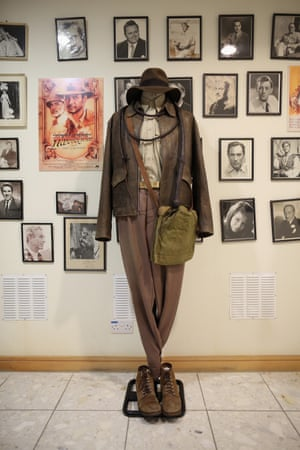 The outfit worn by Harrison Ford in the film Indiana Jones is displayed near actors' headshots and movie stills