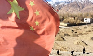 A Chinese flag flies over Tashkurgan, a tranquil frontier town on China's border with Pakistan, which is bracing for change as President Xi Jinping kicks off what some call the most ambitious development plan in history, the 'Belt and Road initiative.
