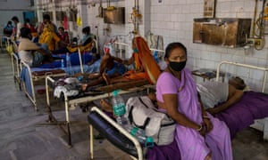 Covid-19 patient Parsada Sah, 67, a shopkeeper, lies on a hospital bed as his wife Vimla Devi, 62, sits next to him in the emergency ward in Bhagalpur, Bihar state, India.