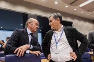 Spanish Economy Minister Luis de Guindos, left, speaks with Greek Finance Minister Euclid Tsakalotos.