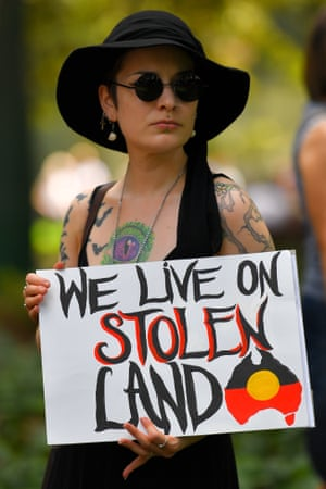 A protestor holds a placard during an Invasion Day rally in Sydney.