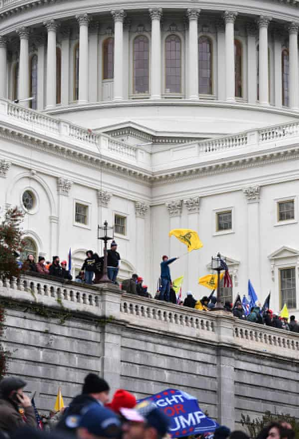 A man waves a Gadsden flag (a flag with a rattlesnake) as Trump supporters storm the US Capitol in January.