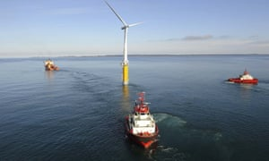 Three red-hulled vessels at sea surrounding a giant three-bladed turbine
