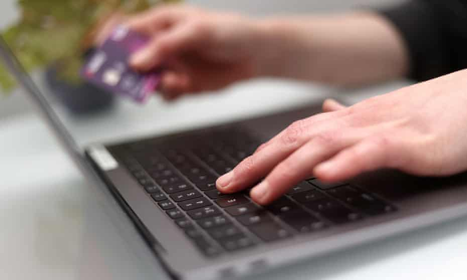 A woman using a laptop as she holds a bank card