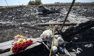 Photo taken on 26 July 2014 shows flowers and a teddy bear, left by parents of an Australian victim of the crash, laid on a piece of the Malaysia Airlines plane MH17, near Hrabove in the Donetsk region.