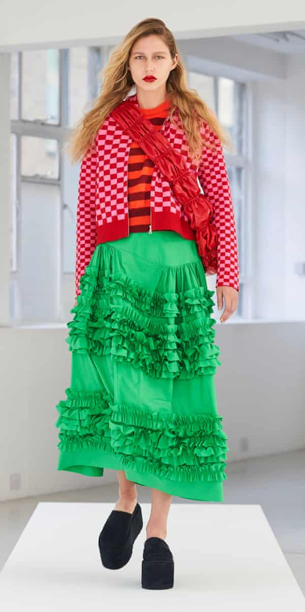 A model in a red top and green flouncy skirt