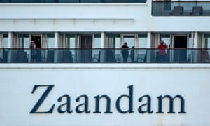 Passengers use binoculars onboard Holland America's cruise ship Zaandam as it entered the Panama City bay to be assisted by the Rotterdam cruise ship with supplies, personnel and Covid-19 testing devices, eight milles off the coast of Panama City, 27 March, 2020.