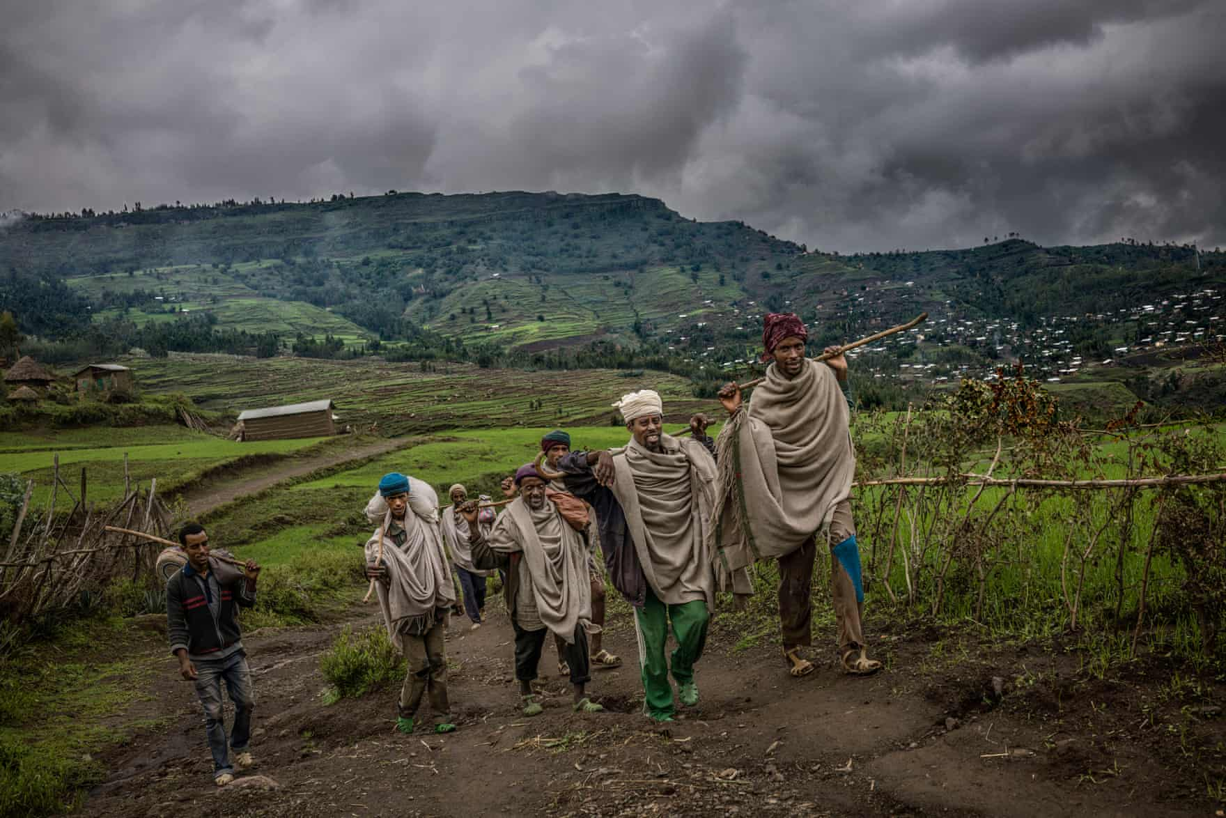 A group of men walk back to their village. Walking is the most common mode of transport in the highlands, where there are few motorbikes and people often have to cross difficult terrain to reach the nearest town via The Guardian