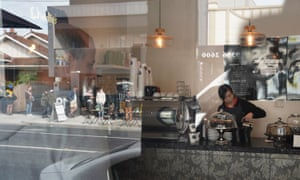A women makes a coffee in a cafe while across the road people queue outside a Centrelink office in Melbourne