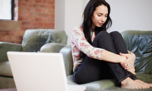 Woman sitting on sofa with her laptop nearby