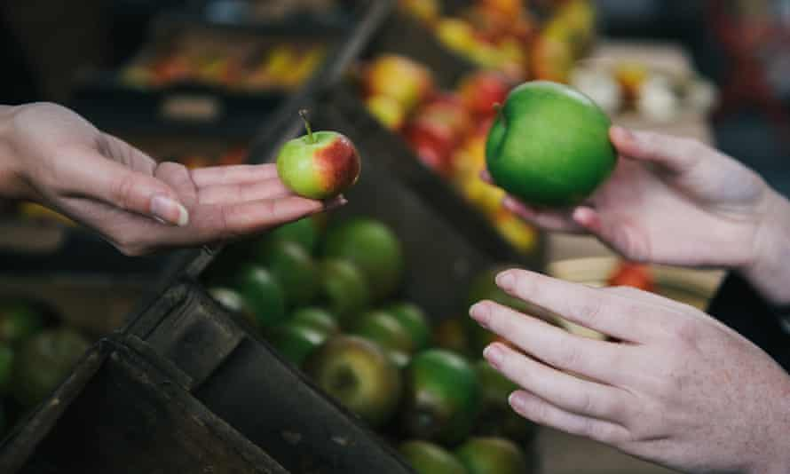 Apple amnesty: a customer hands over a granny smith in exchange for a rare British apple at Borough Market in London