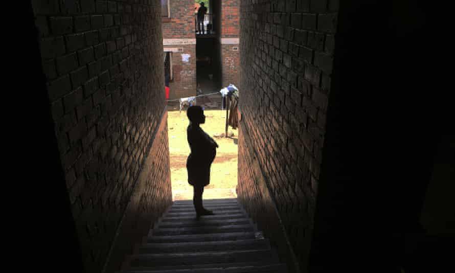 A pregnant woman waits in a passageway