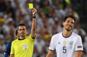 Mats Hummels walks away in disbelief after being shown the yellow by Viktor Kassai.