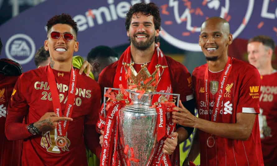 Liverpool's Roberto Firmino, Alisson and Fabinho pose with the Premier League trophy.