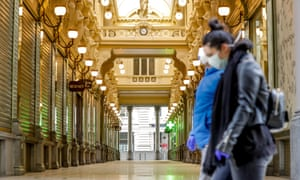 Women wearing masks pass by closed shops of Passage du Nord Gallery in Brussels city centre, Belgium.