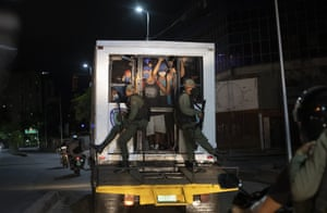 Men are detained in a police van for not complying with Covid-19 regulations by breaking curfew or attending block parties in the neighbourhood of Petare