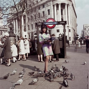 A woman stands near pigeons at Trafalgar Square