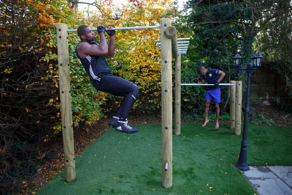 Daniel Dubois performing pull-ups with his younger brother Prince in the back garden of his home