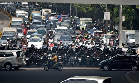 Commuters at a busy intersection in Jakarta.