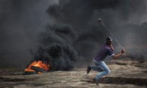 Palestinians burn tyres and throw rocks with slingshots in response to Israeli forces' intervention during a protest in the Great March of Return.