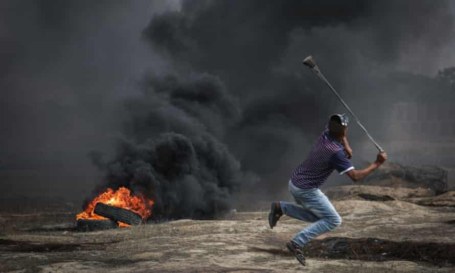 Protesters burn tyres and throw rocks at Israeli forces near the Gaza-Israel border on 11 May.