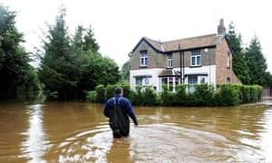 A man wades through flood water near Pickering, North Yorkshire