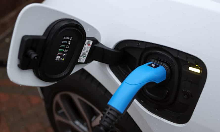 An electric charging cable connected to a Jaguar I-Pace electric car at a residential home.