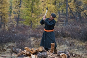 A man who is part of the nomadic tribe seen chopping up wood to create a fire in East Taiga, Mongolia