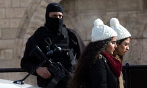 Palestinian women walk past an Israeli police officer standing guard at Damascus gate of the Old City of Jerusalem