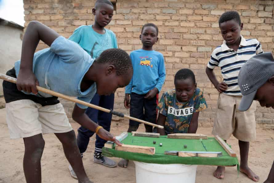 Children play on a makeshift pool table, Hopley, Harare