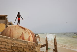 A child plays on the ruins of a sea wall