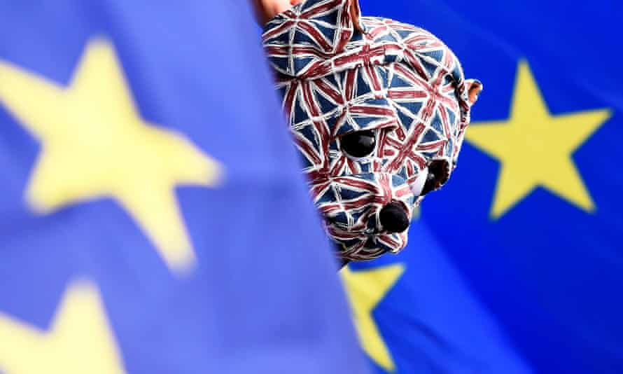 A British bulldog toy peeping out from EU flags