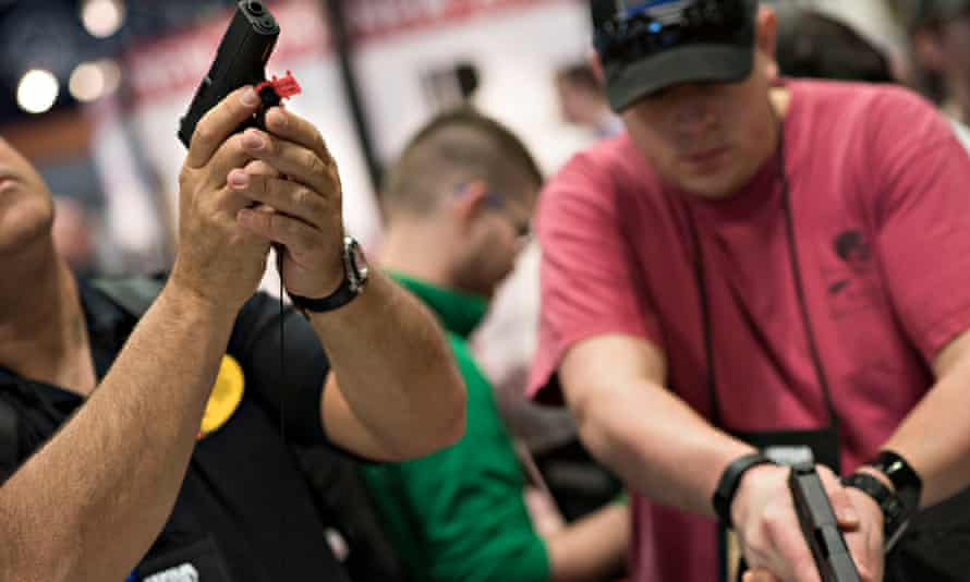 Attendees look over Glock pistols at an NRA meeting in Tennessee. With Donald Trump in power, Congress could pass a law ending local gun restrictions.