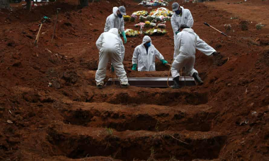 Gravediggers wearing protective suits bury the coffin of Jose Soares, 48, who died from Covid-19, at São Luiz cemetery, in São Paulo, Brazil, on Thursday.