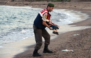 A police officer carries the lifeless body of Alan Kurdi