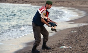 A paramilitary police officer carries the lifeless body of Aylan Kurdi after the boat carrying his family to the Greek island of Kos capsized near the Turkish resort of Bodrum on Wednesday 2 September.