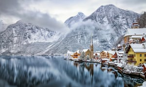 Snowcapped mountains and colourful houses by a lake