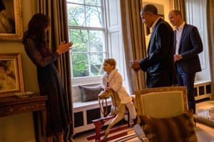 Barack Obama and the Duke of Cambridge look on while the Duchess of Cambridge draws Prince George's attention.