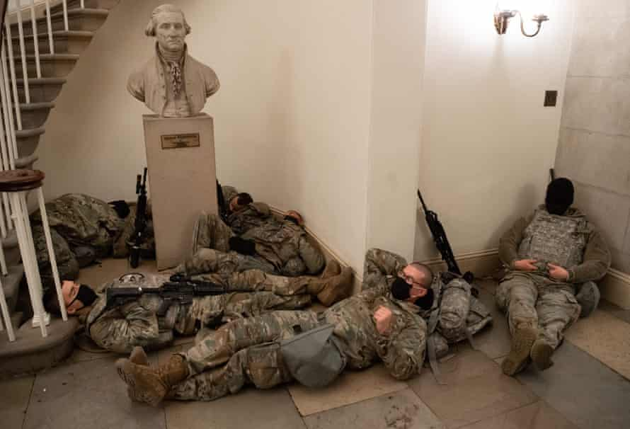 National Guard take a rest in the Rotunda of the US Capitol below a bust of George Washington.