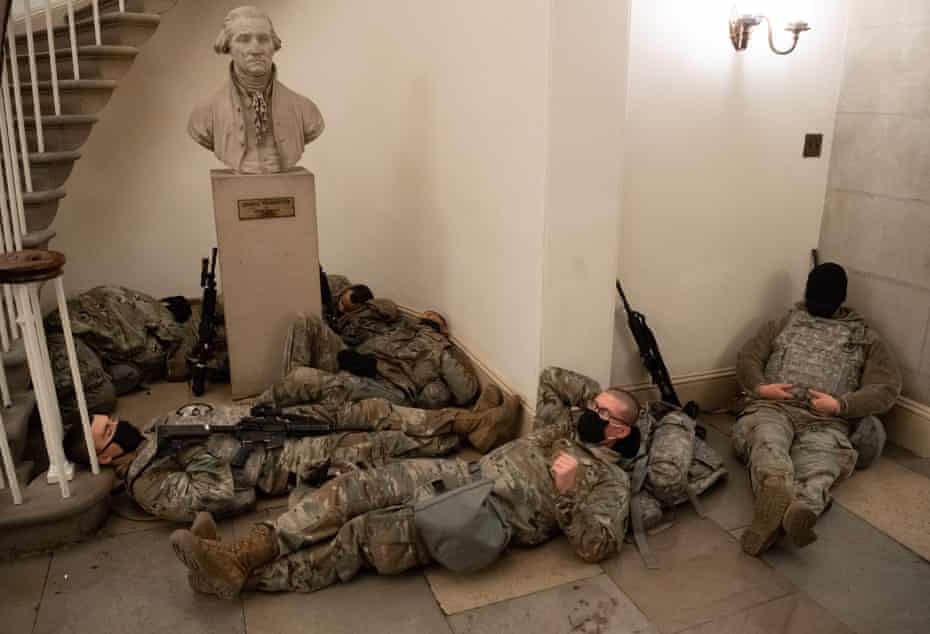 Members of the National Guard take a rest in the Rotunda of the US Capitol in Washington, DC, January 13, 2021, ahead of an expected House vote impeaching US President Donald Trump.