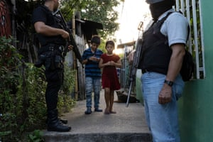 Residents in a low-income settlement (controlled by MS 13) pass by a police patrol, San Martín, San Salvador.