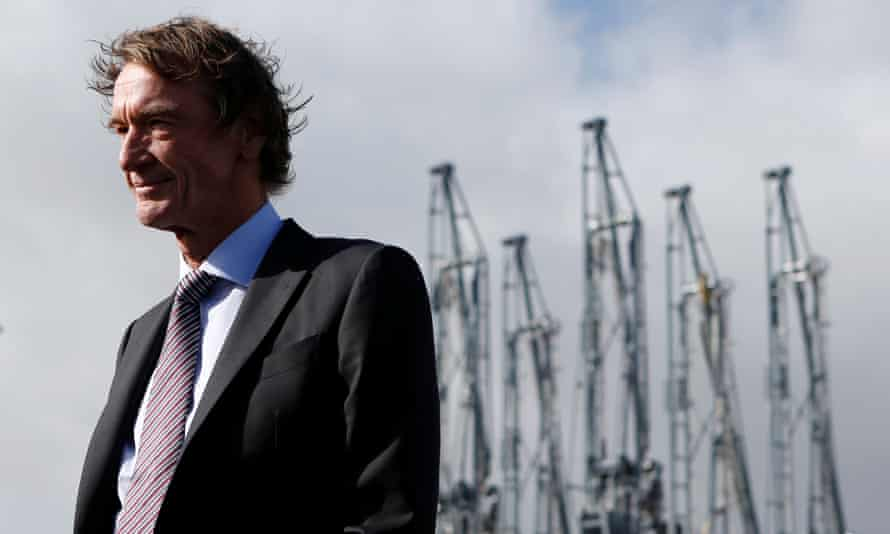Jim Ratcliffe in a suit and tie, photographed from the side outdoors with a row of cranes behind hin