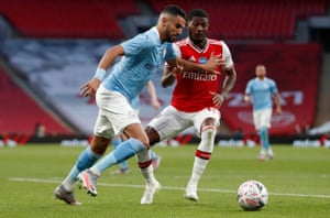 Manchester City's Riyad Mahrez attempts to get the better of Arsenal's Ainsley Maitland-Niles.