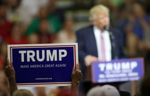 A supporter of Donald Trump holds up a sign.