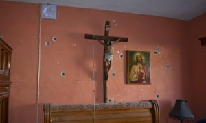 A wall of the room of a home is riddled with bullet holes after a gun battle between Mexican security forces and suspected cartel gunmen.