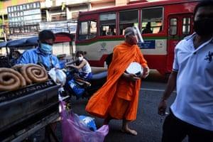 Bangkok, Thailand A Buddhist monk collects alms at an outdoor market in Bangkok