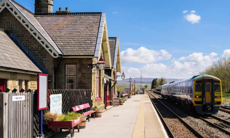 Passenger train leaving Ribblehead station on Settle to Carlisle railway line. Yorkshire Dales National Park West Riding, North Yorkshire, England, UK.